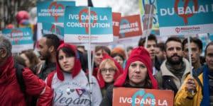 Dans la manifestation, des gens portent des pancartes : « Du balai ! », « IVG dans la Constitution », etc.